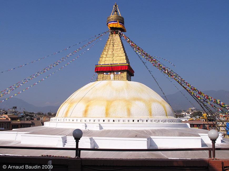 Photographie d'un Stupa, monument emblématique du bouddhisme, dôme blanc surmonté d'une flèche dorée à base carrée qui s'élève par échelons comme une pyramide